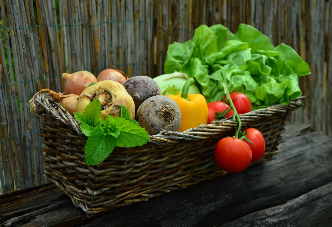 Red Tomato Besides Green Vegetable Leaf on Brown Basket