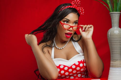 Woman in White and Red Polka Dot Spaghetti Strap Top Wearing Sunglasses