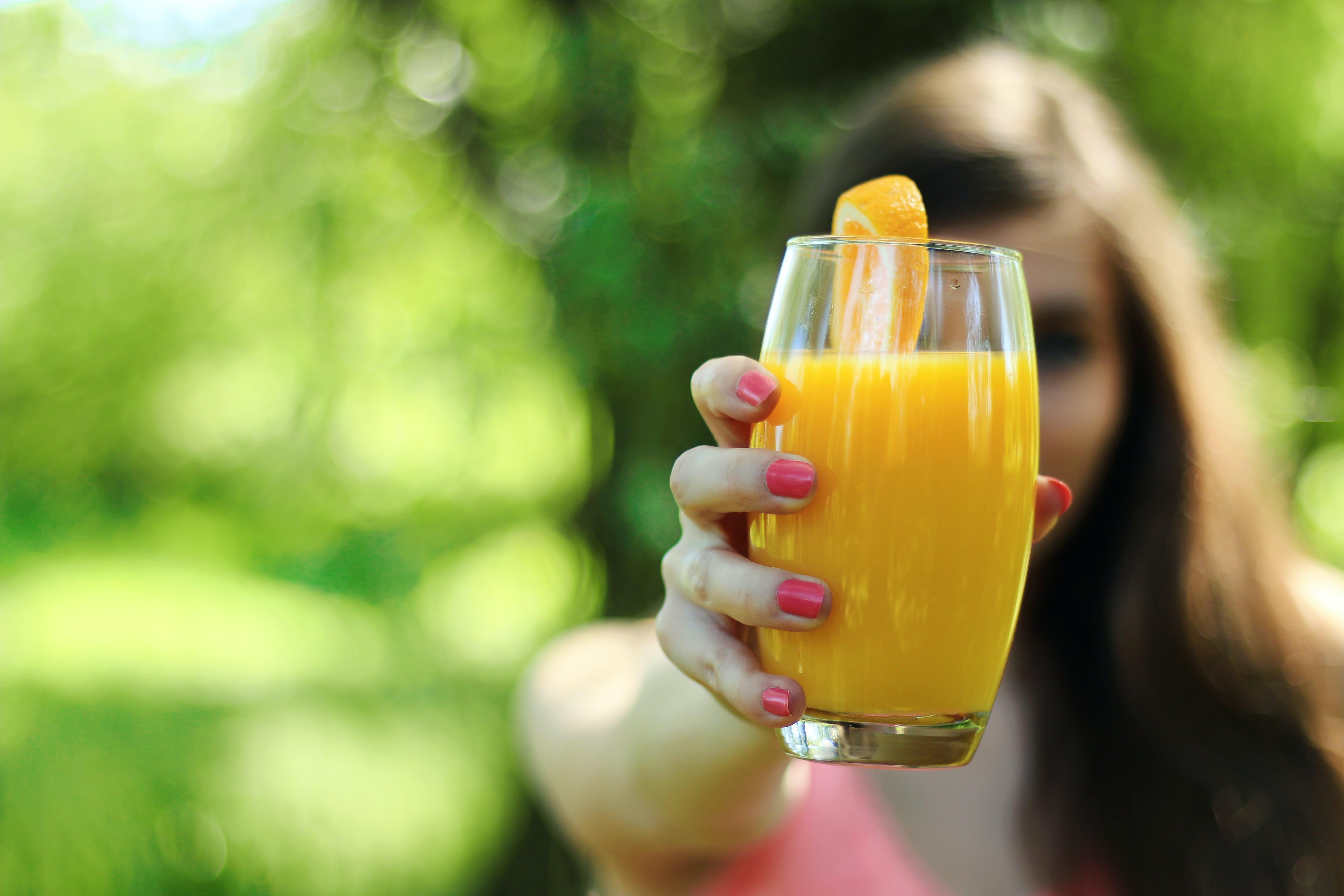 Woman in Pink Top Holding Orange Juice in Glass Cupo