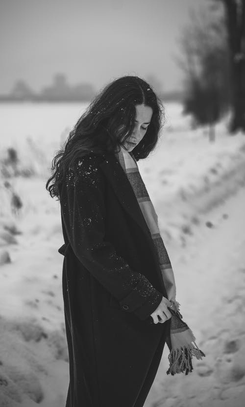 Gray scale Photo of Woman in Black Trench Coat Standing on Snow Covered Ground