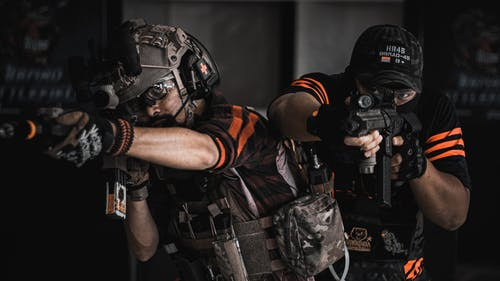 Two Man Pointing Gun Wearing Black And Orange