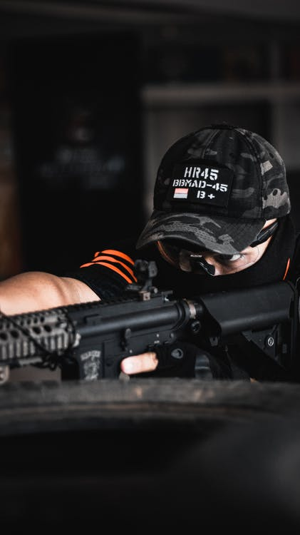Person Wearing Camouflage Cap Holding Rifle