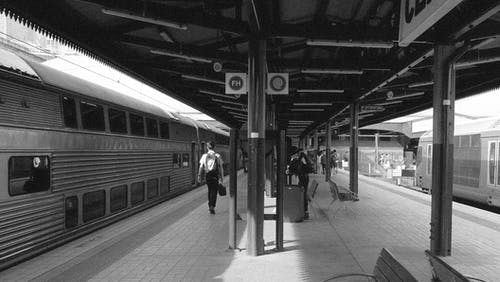 Grayscale Photo of People Walking on Train Station