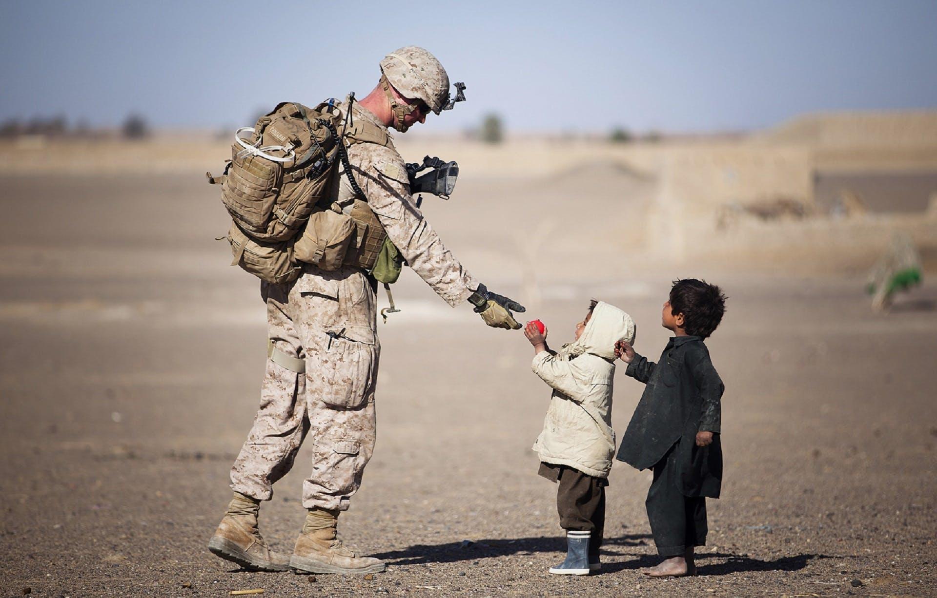 military man helping children