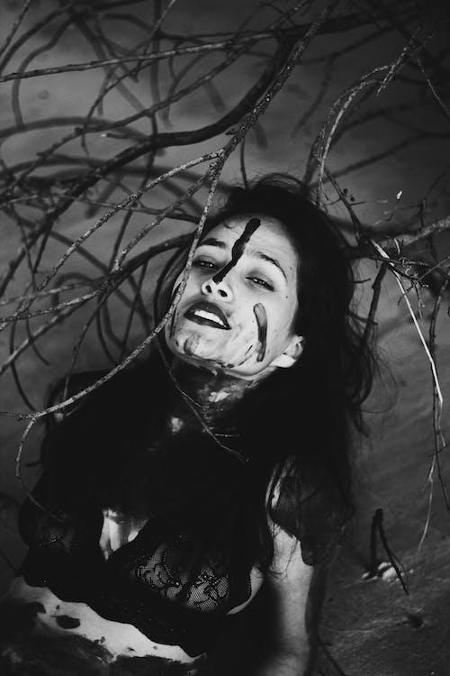 Monochrome Photo of Woman  Behind Tree Stem