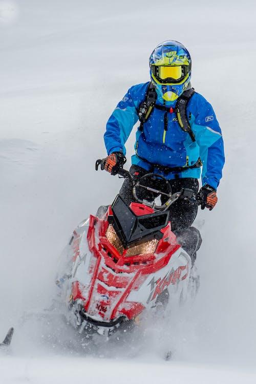 穿著藍色夾克和頭盔的男人騎紅雪移動