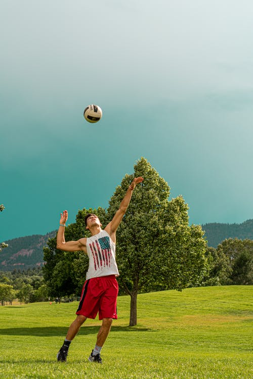 Man in White Tank-top and Blue Shorts Standing on Green Grass Field Playing with Soccer Ball