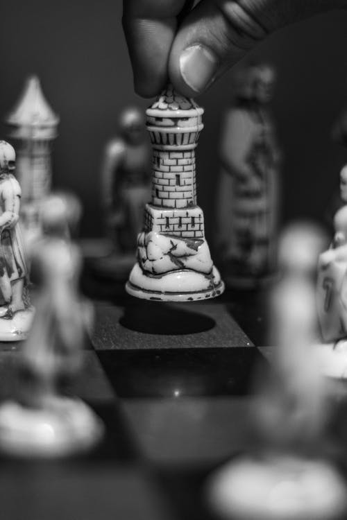Gray scale Photo of Person Holding Chess Piece