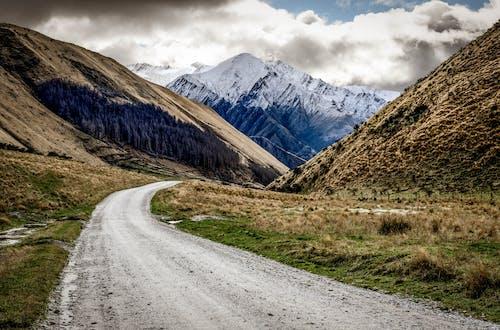白い曇り空の下の茶色と緑の山の近くの灰色のアスファルト道路