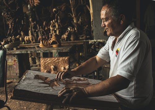 Man in White Polo Shirt Working on Wooden Sculpture