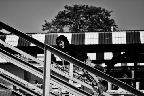 Black and white side view of barefoot boy in hoodie rolling down railing while spending summer time outdoors