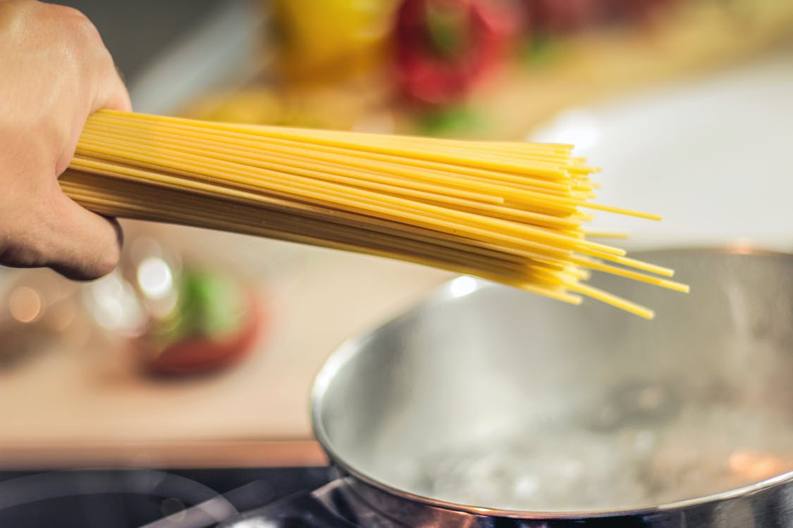 Person Holding Raw Pastas Aiming at Boiling Water in Pot