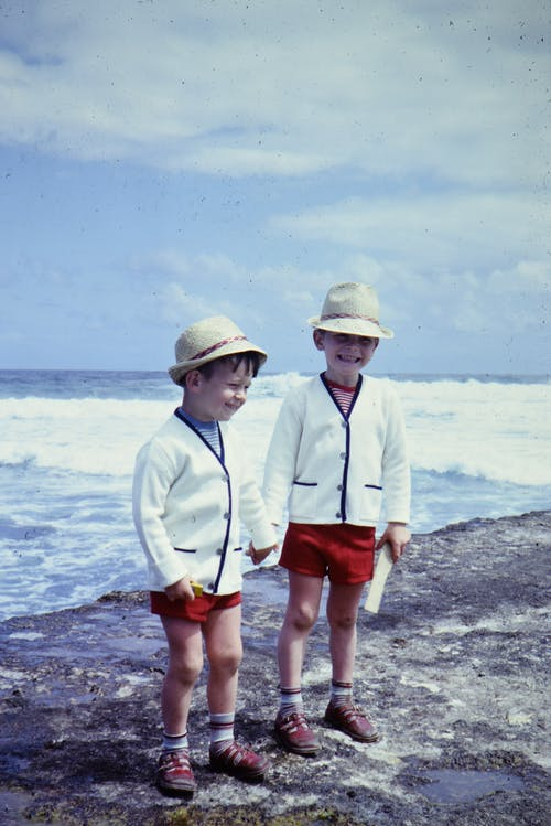 Two Boys in White Sweaters and Red Shorts Standing on Beach