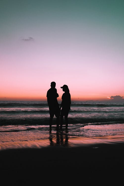 Silhouette of Couple Standing on Beach during Sunset