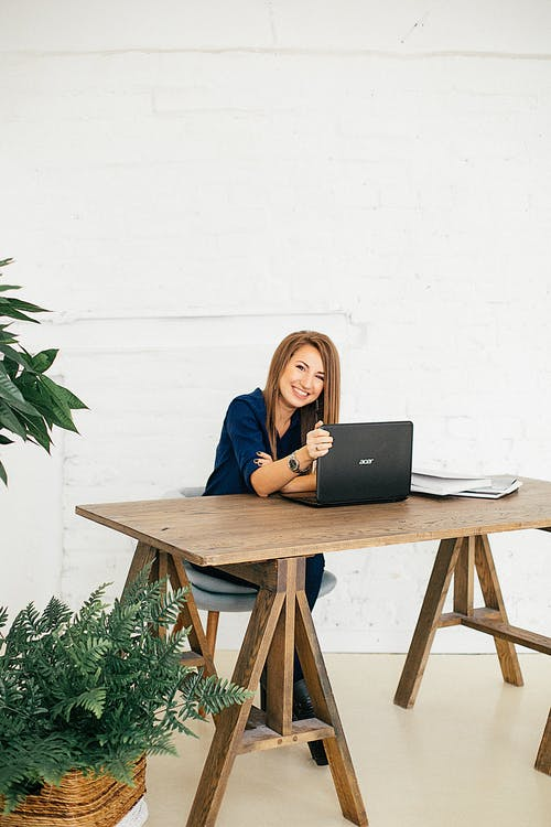 Woman In Wooden Table Using Computer Behind White Wall
