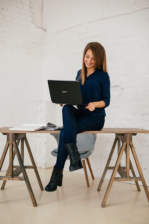 Woman in Blue Long Sleeve Blouse and Blue Pants Sitting on Brown Wooden Stool