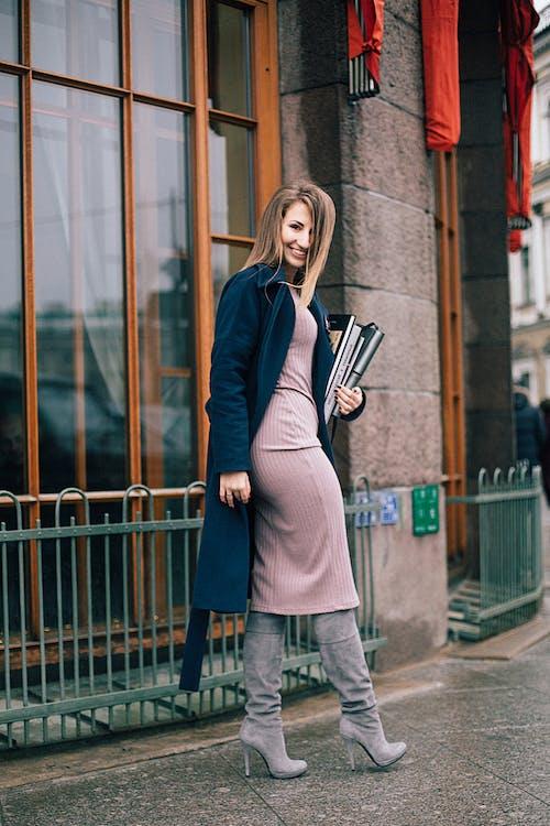 Woman in Blue Coat Standing Beside Metal Fence