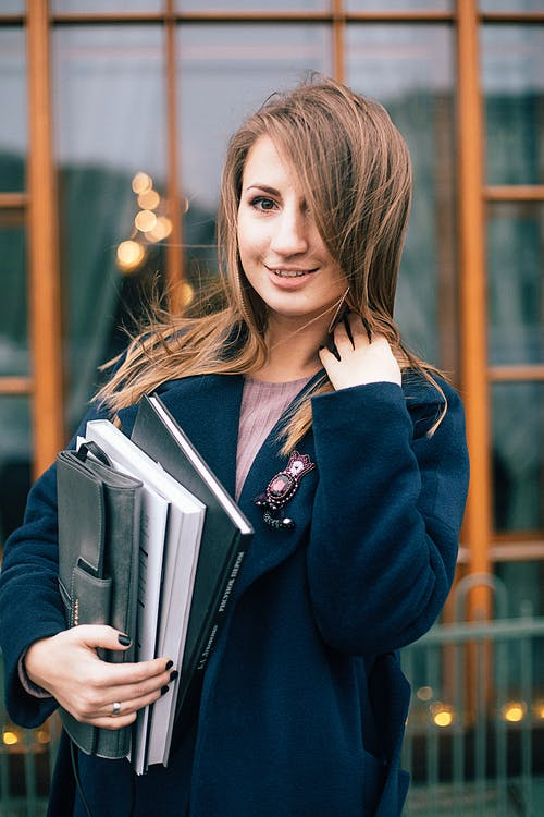 Woman in Blue Blazer Holding Books