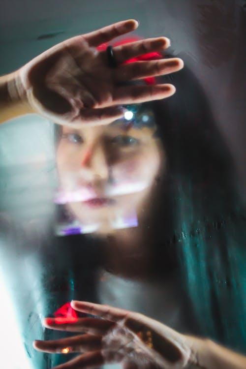 Ethnic thoughtful woman looking through window