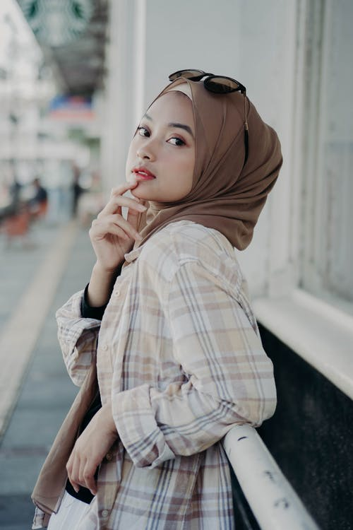 Woman in Brown Hijab and White Brown and White Plaid Long Sleeve Shirt Leaning on Metal Railing
