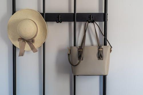 Black Metal Hook Hanging a Beige Hat and Grey Sling Bag
