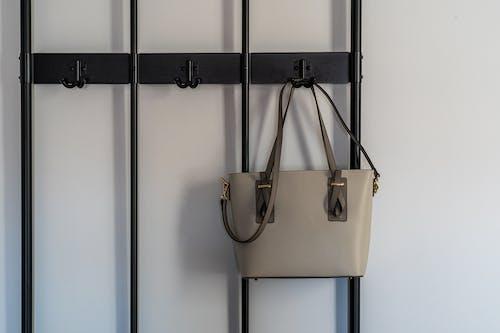 Sling Bag Hanging on Black Metal Holder
