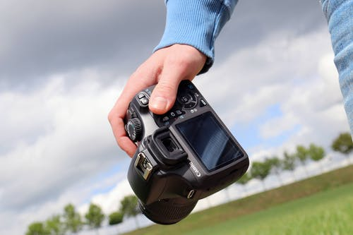 Person Holding Canon Dslr Camera