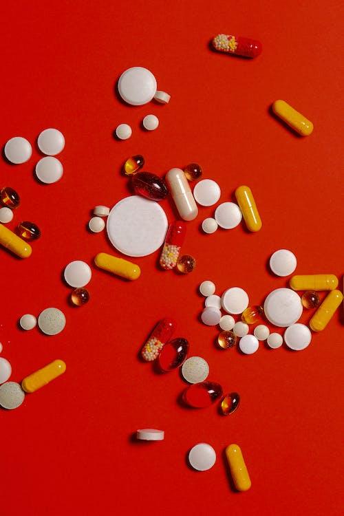 Таблетки и капсулы различных лекарств на красном фоне