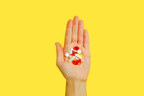 Person With Bunch Medication Pills on Hand