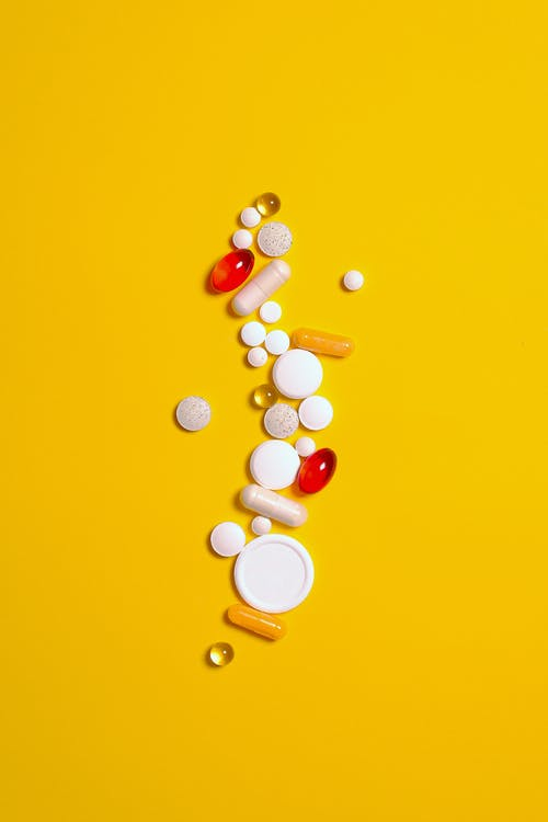 Medication Pills and Capsules Isolated on Yellow background