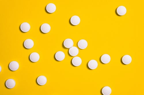 White Medication Pills Isolated on Yellow background