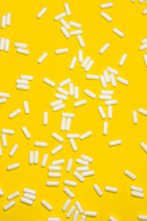 White pills Isolated on Yellow background