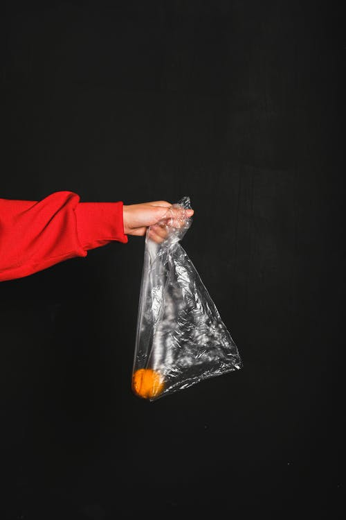 Person in Red Long Sleeve Top Holding Colorless Plastic Bag and Yellow Fruit Inside