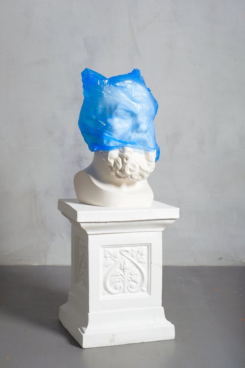 A Photo Of A Carved Statue Covered In A Blue Plastic