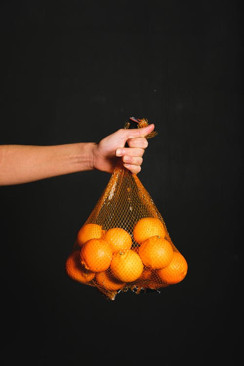 Person Holding Orange Net and Bunch of Orange Fruits