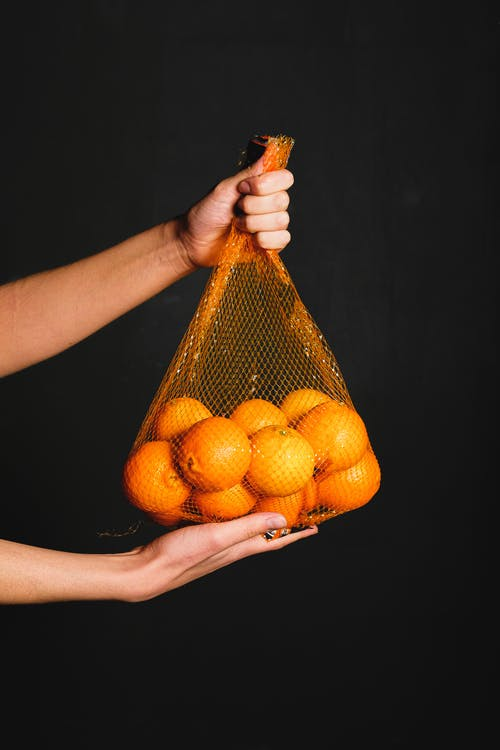 A Fresh Orange Inside Of A Fruit net