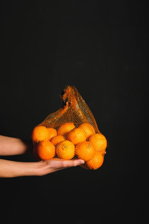 Person Holding Bunch of Fruits on Black Background