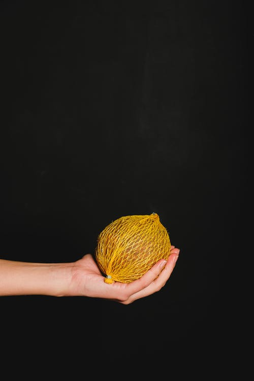Person Holding A Fruit Covered in Yellow Yarn