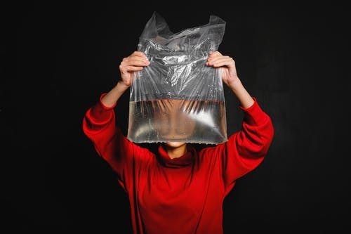 Person in Red Long Sleeve Top Holding Black Plastic Bag with Water Inside