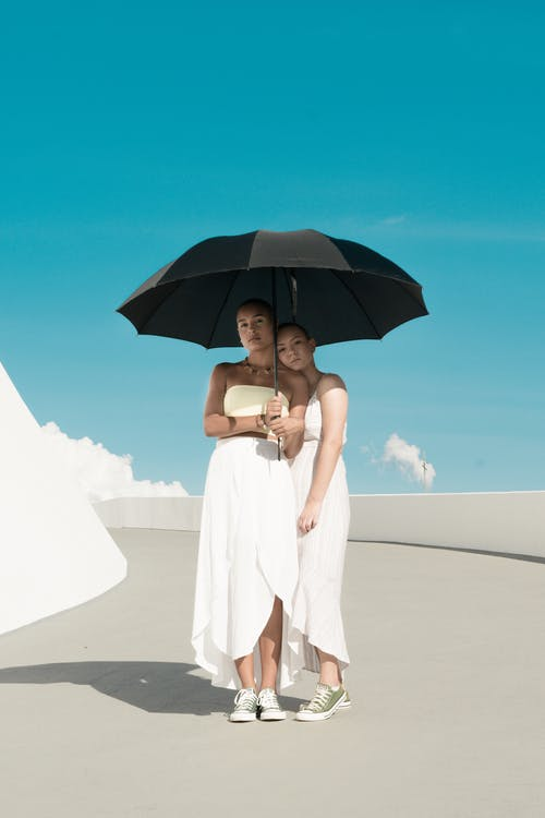 Two Woman in White Dress Holding Black Umbrella Under Blue Sky