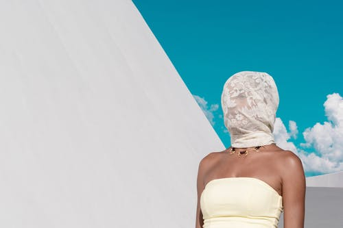 Woman in White Tube Top Covering Her Face With Veil