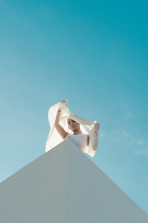 Low Angle Shot on Woman Under Blue Sky