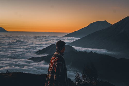 Man Standing on Top of the  Mountain during Sunset