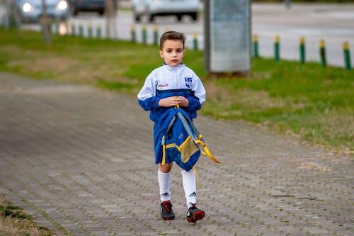 Boy Wearing White Blue Jacket Walking on Brick Wall