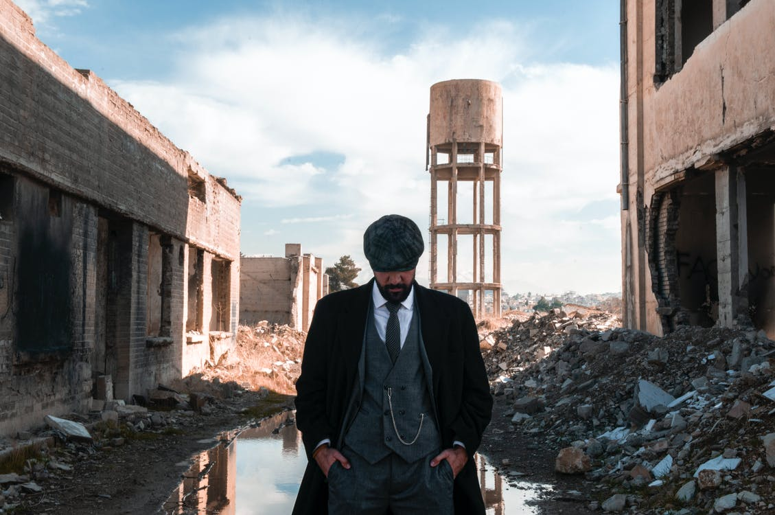 Respectable black man standing with hands in pockets in ruins
