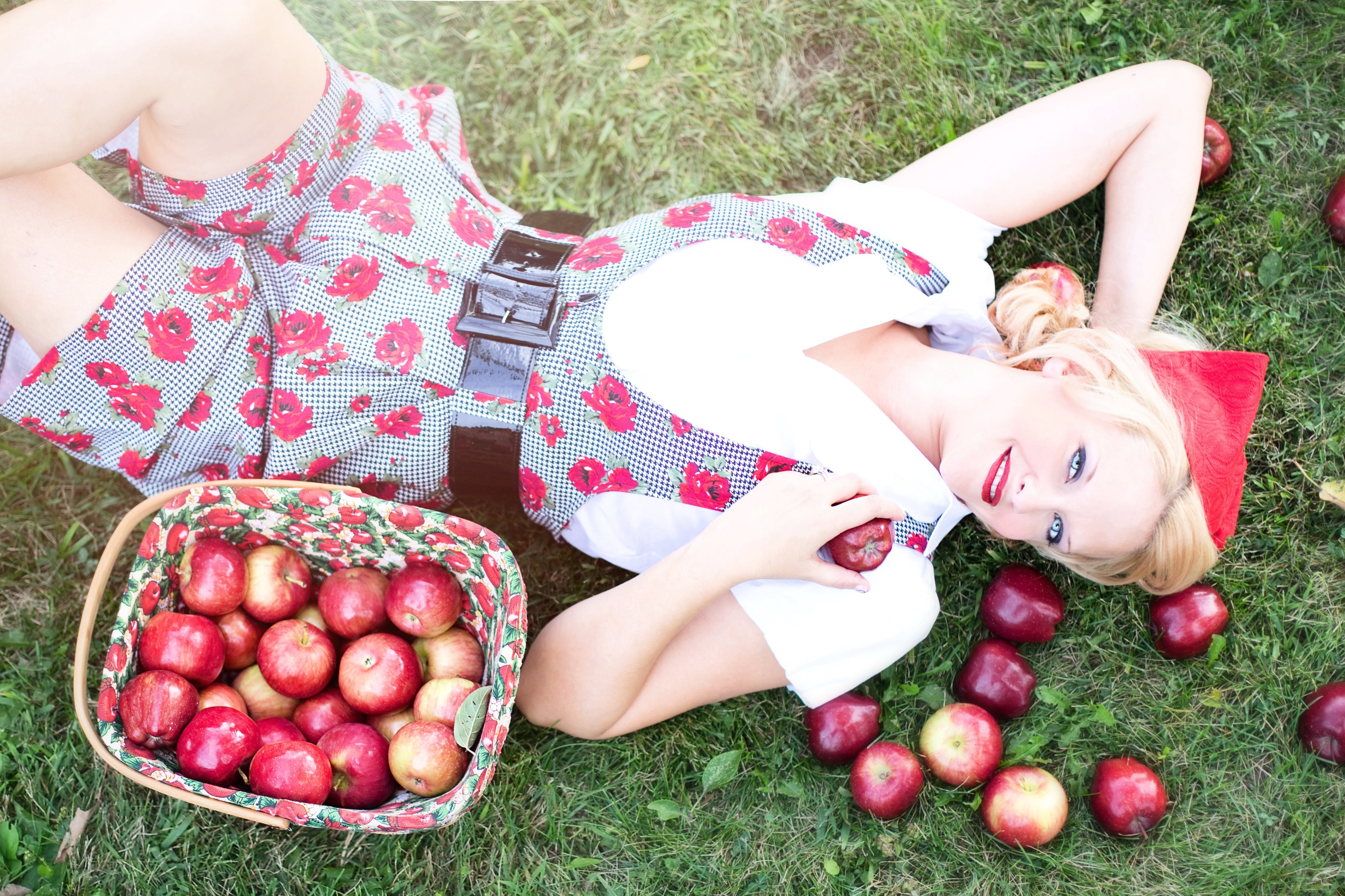 Woman in Gray and White Rose Print Onesies Laying on Grass Beside Red Apple Fruits