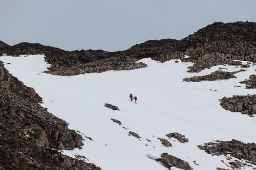 People Walking on Snow Capped  Mountain