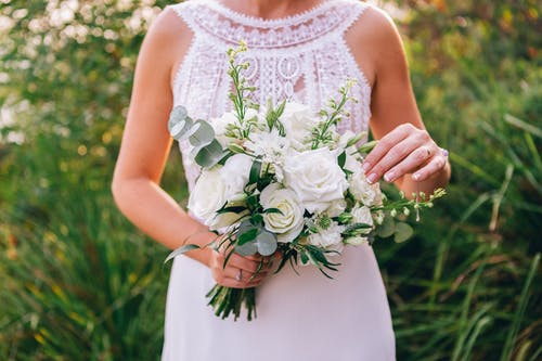 Woman in White Floral Sleeveless Dress Holding White Rose Bouquet