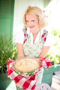Woman in Pink White Floral Apron Smiling While Holding a White Creme Food during Daytime