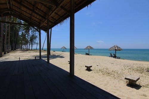 Immagine gratuita di acqua, alberi, capanna in spiaggia, cielo azzurro